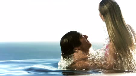 kaluž : Couple embracing in a swimming pool in slow motion