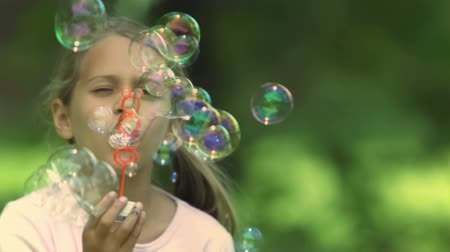 bańki mydlane : Little girl in slow motion blowing bubbles in a park