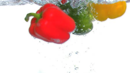 groene pepers : Peppers duiken in het water in super slow motion in studio