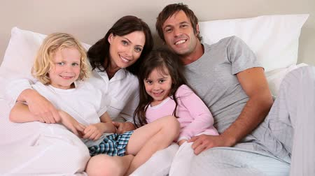родной брат : Smiling family lying in a bright bedroom