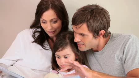 ler : Smiling family reading a book aloud in a bedroom