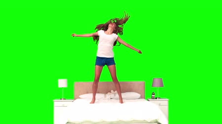 salto : Woman jumping in slow motion on her bed against a green background