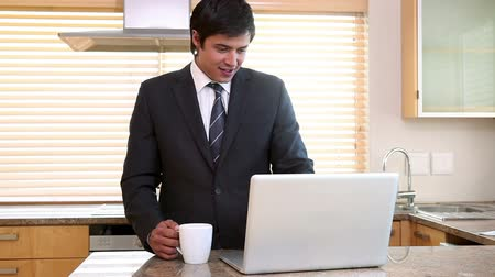 káva : Young businessman drinking coffee while using his laptop in the kitchen