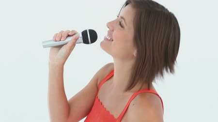 śpiew : A girl singing into a microphone against a white background Wideo