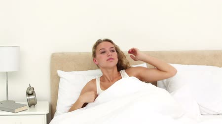 double happiness : Blonde haired woman wakes up and yawns in her bed