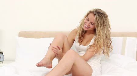 nogi : Blonde applying moisturiser cream on her legs on her bed Wideo