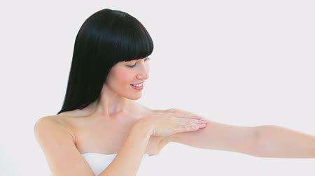 towel : Smiling woman massaging her arm against a white background