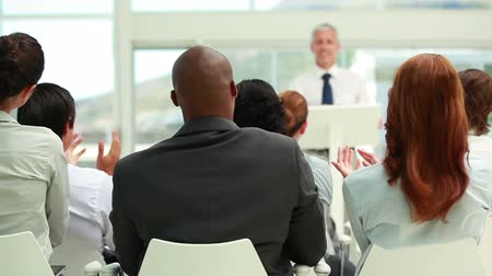 Business people listening to a speaker in a conference room