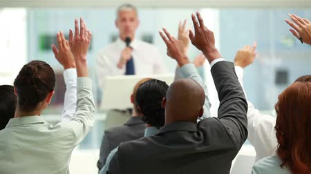 Business people raising their hands together in a conference room