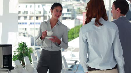 oblek : Woman drinking a cup of coffee before shaking hands in an office