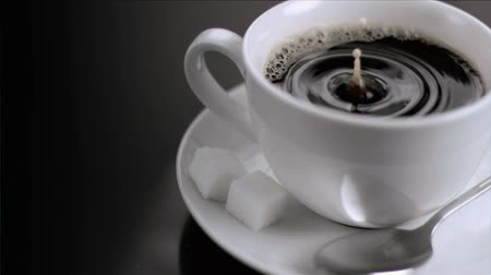 xícara de café : A drop falling in super slow motion in a cup of coffee