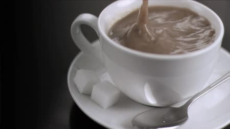 сахар : Sugar cube falling in super slow motion in a white coffee cup Стоковые видеозаписи