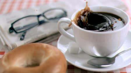 кофе : Sugar makes coffee splashes in super slow motion on glasses and newspaper Стоковые видеозаписи
