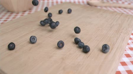 jagoda : Blueberry falling in super slow motion on a wood board in a kitchen