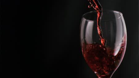 Red wine flowing in super slow motion in a wine glass