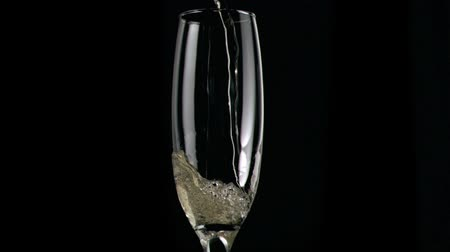 šampaňské : Champagne being poured in super slow motion in glass against black background