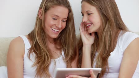 dokunaklı : Happy brunette friends looking at a tablet computer in a bedroom