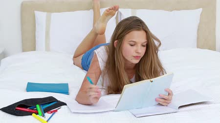 fekvő : Serious brunette woman writing a text while lying in her bedroom Stock mozgókép