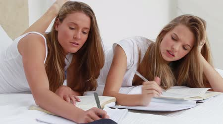 yatarken : Serious young women studying while lying in a bedroom