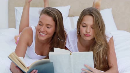 ложь : Friends reading books while listening to music together in a bedroom Стоковые видеозаписи