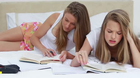 ležící : Serious friends doing their homework together in a bedroom