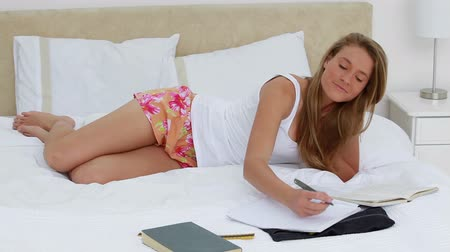 ler : Peaceful student doing her homework while lying in her bedroom