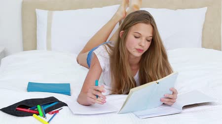 yatarken : Serious young woman studying while lying in her bedroom Stok Video
