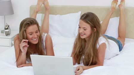 ложь : Happy women lying while looking at a laptop in a bedroom