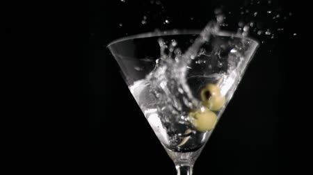 martinis : Olive skewer falling in super slow motion in a glass against a black background
