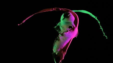 colorful drops : Pink and green paints in super slow motion mixing against a black background