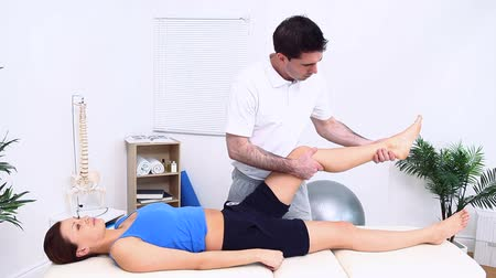 terapeuta : The leg of a woman being stretched by a physiotherapist in a room Stock Footage
