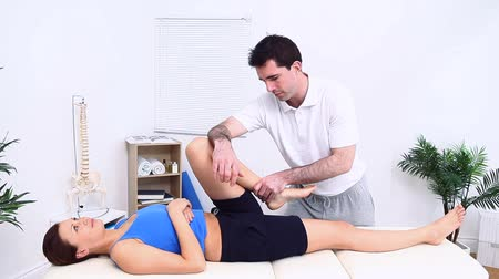 mobilization : Physiotherapist manipulating a knee in a room Stock Footage