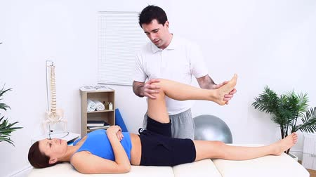 mobilization : Physiotherapist massaging the knee of a patient in a therapy room