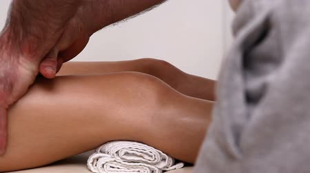 mobilization : Physiotherapist massaging the upper part of the knee of a patient in a therapy room Stock Footage