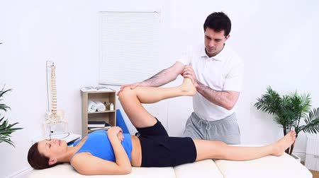 terapeuta : Physiotherapist stretching the leg of his woman patient in a therapy room Stock Footage