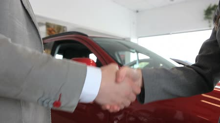 red tie : Close up of people shaking hand in a dealership
