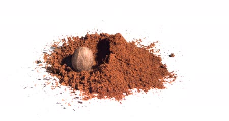tandoori : Nutmeg falling in super slow motion into brown powder against white background Stock Footage