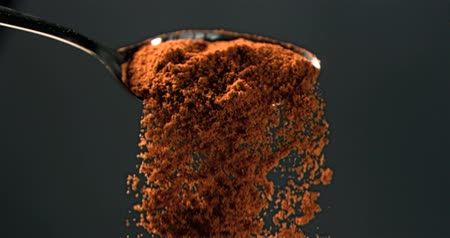 ложка : Masala powder falling in super slow motion of a spoon against black background