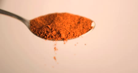 pão de especiarias : Masala powder falling in super slow motion from a spoon against tan background