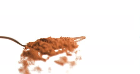 skořice : Cinnamon powder falling in super slow motion from a spoon against white background Dostupné videozáznamy