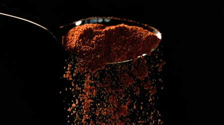 pão de especiarias : Orange powder falling in super slow motion out of a spoon against a black background Stock Footage