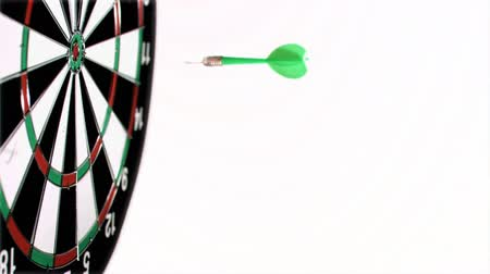 цель : Dart being thrown in super slow motion on a dart board against a white background