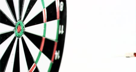okçuluk : Plastic red dart in super slow motion being thrown on a dart board against a white background Stok Video