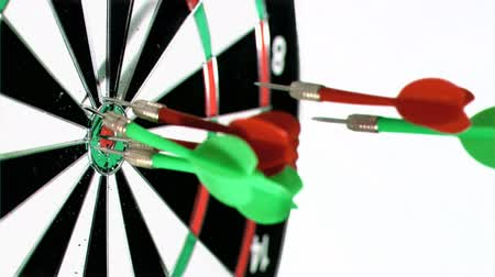 nyilak : Green and red darts in super slow motion thrown at a dart board against a white background Stock mozgókép