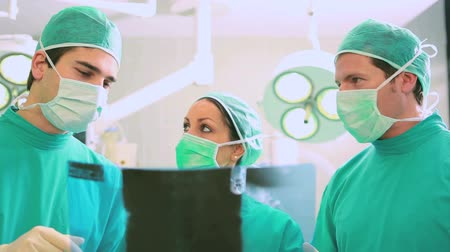 cerrahi : Close up of a surgical team analysing a Xray in an operating theatre Stok Video