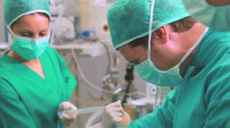 operasyon : Video of a surgeon team operating in an operating theatre Stok Video