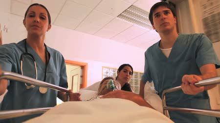 acil durum : Nurses driving a patient on his bed with an oxygen mask in a hallway in a hospital