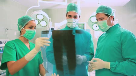 cirurgião : Close up of a surgical team analysing a Xray in an operating theatre Stock Footage