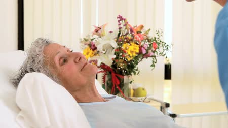 canteiro de flores : Senior patient with a smiling nurse in a hospital room