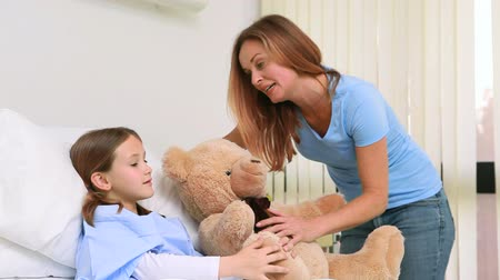 paediatrician : Smiling woman while giving a teddy bear to a girl in a hospital bed with balloons